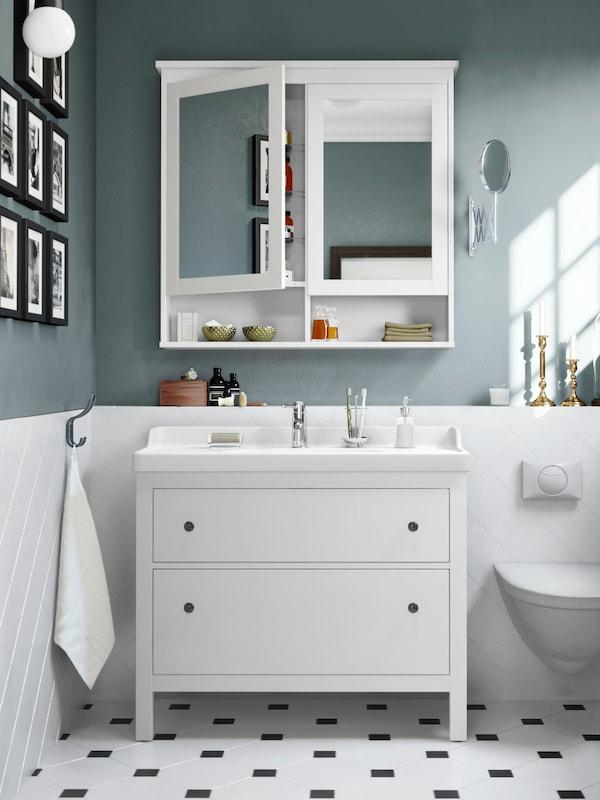 그레이/화이트 욕실 두 개의 서랍이 있는 화이트 세면대, 두 개의 도어가 있는 화이트 거울 수납장이 있고 벽에는 사진이 걸려 있어요.