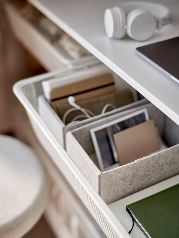 Egy félig kihúzott hálós kosarat látunk, amelyet világos szürke, puha filcből készült KOMPLEMENT dobozokkal egészítettek ki. Ezekben, ahogy látjuk, jól elfér a notebook, a fejhallgató és még sok minden más.