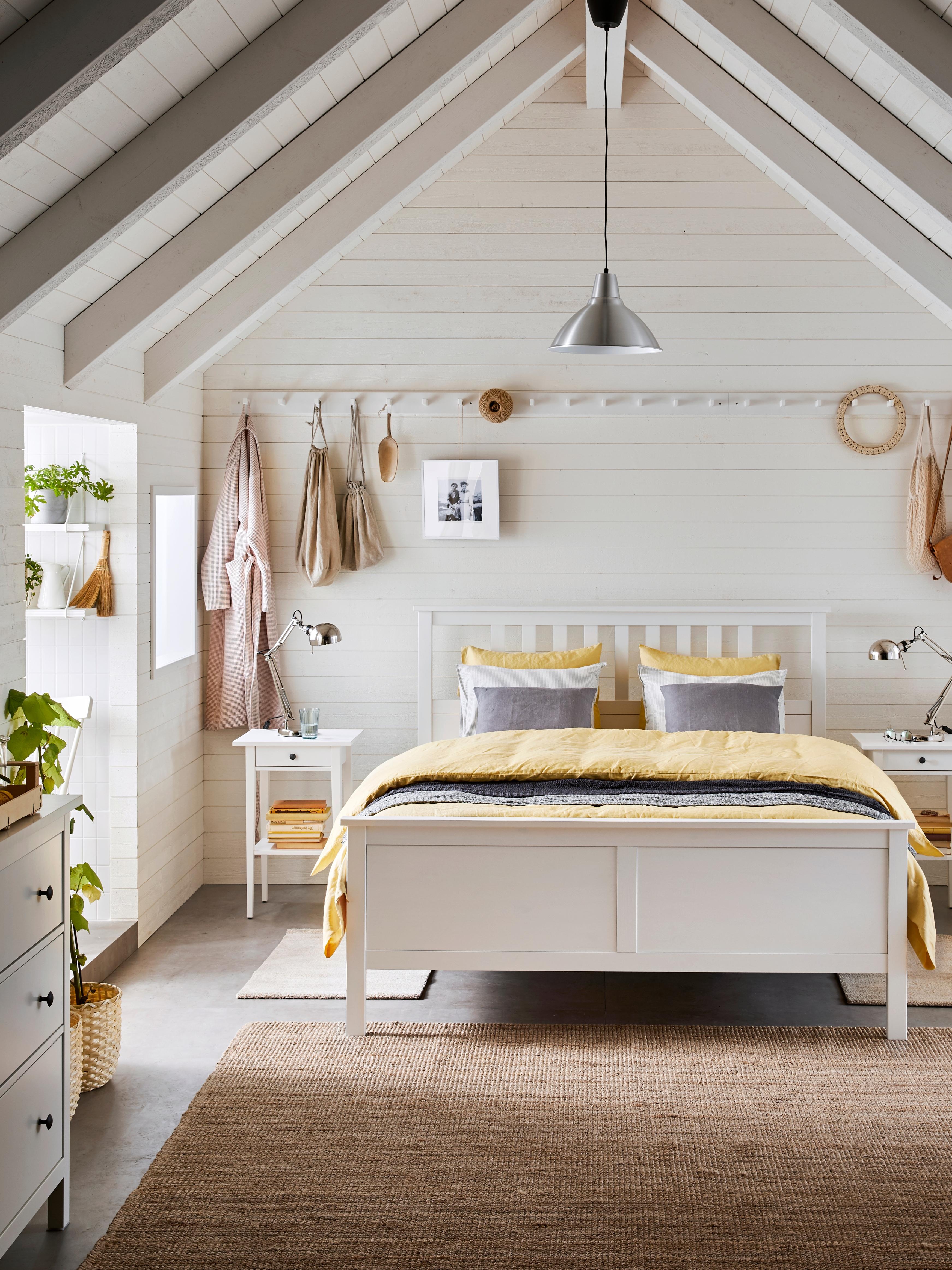 Letto HEMNES bianco, tappeto in fibra naturale e attaccapanni bianco con ganci appeso alla parete.