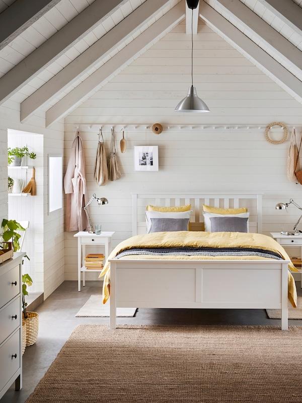Camera da letto in legno bianco con tetto spiovente. Al centro un letto matrimoniale HEMNES bianco con copriletto giallo.
