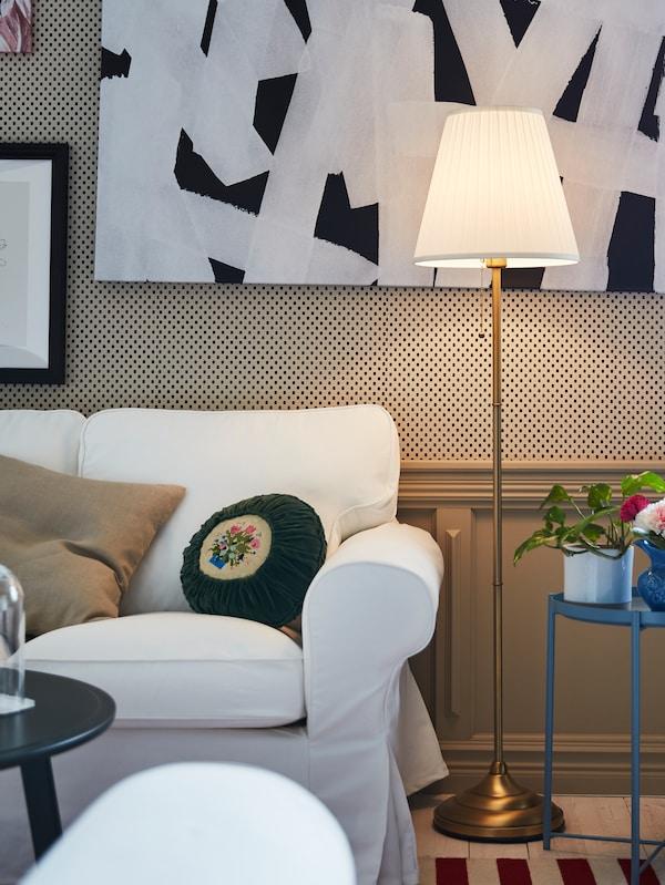 Un soggiorno con una lampada da terra bianca e ottone accanto a un divano EKTORP bianco.