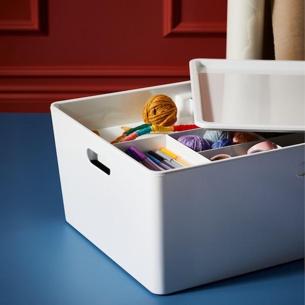 Fehér KUGGIS doboz, a fedele félig félrehúzva, így láthatók a benne lévő KUGGIS betét rekeszeiben tárolt kézműves kiegészítők.