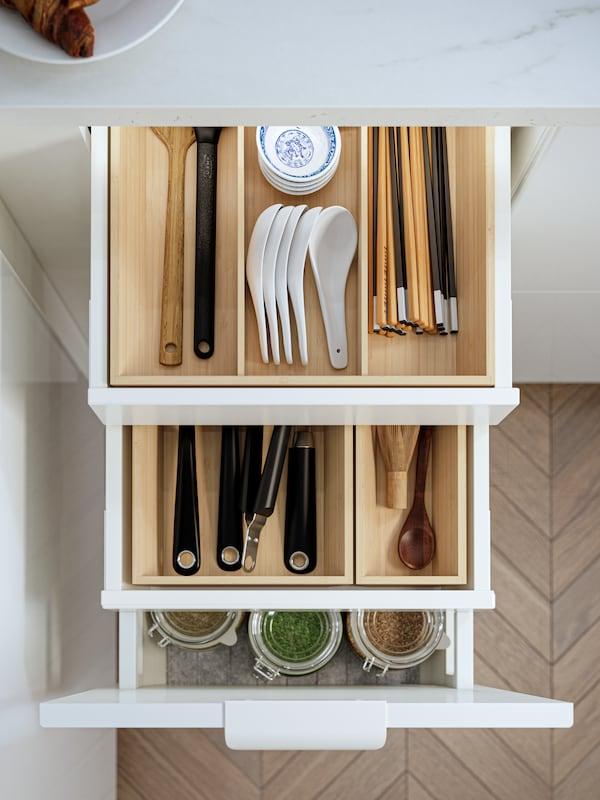 Eine geöffnete Küchenschublade mit UPPDATERA Inneneinrichtungen in hellem Bambus. Zu sehen sind Essstäbchen und andere Küchenutensilien.