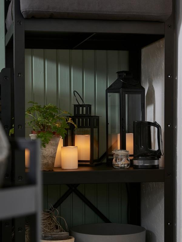 Деревянный садовый стол и стул, на столе стоит фонарь, есть подвесной светильник, на стене деревянная рама с зеленью.