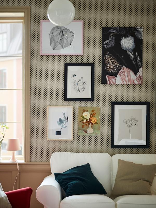 Galleria d'arte composta da cornici trattate con mordente nero e altre cornici, dietro a un divano EKTORP bianco.