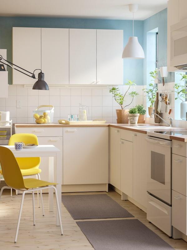 مطبخ زاوية أبيض يحتوي على خزائن قاعدة بيضاء وخزائن حائط بيضاء وطاولة بيضاء صغيرة وكرسيين بلون أصفر.