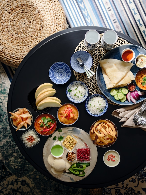 A black KRAGSTA coffee table laden with a meal served on a blue ERTAPPAD dish and in multiple ENTUSIASM bowls and mugs.
