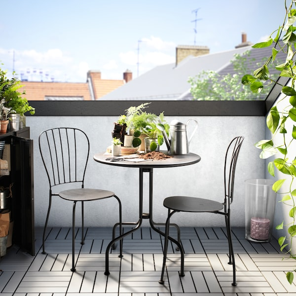 A terrace with an outdoor table with green plants and various items, and two chairs, with a roof-top in the distance.