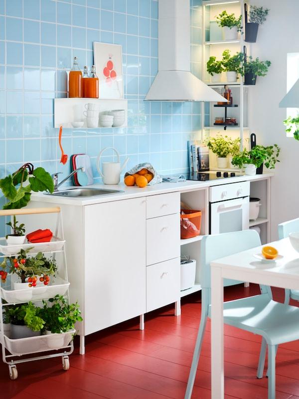 Witte keuken op een rode vloer tegen een lichtblauwe achtergrond.