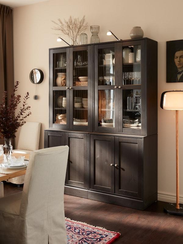 Deux vitrines brun foncé où sont exposés des verres et de la vaisselle, surmontées d'éclairages intégrés.
