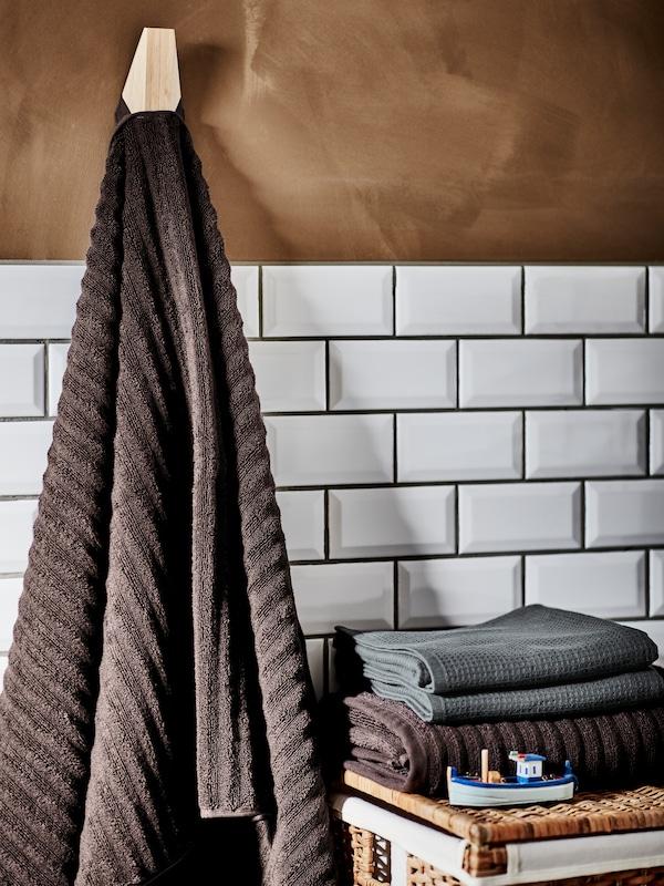 Темно-коричневий банний рушник висить на SKUGGIS СКУГГІС бамбуковому гачку, складені рушники лежать на кошику для білизни на фоні білої кахляної стіни.
