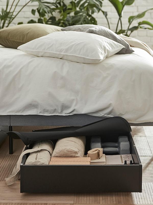 صندوق تخزين تحت السرير VARDÖR منظم بعناية تم سحبه من أسفل السرير به أغطية لحاف ÄNGSLILJA وثلاث وسائد.