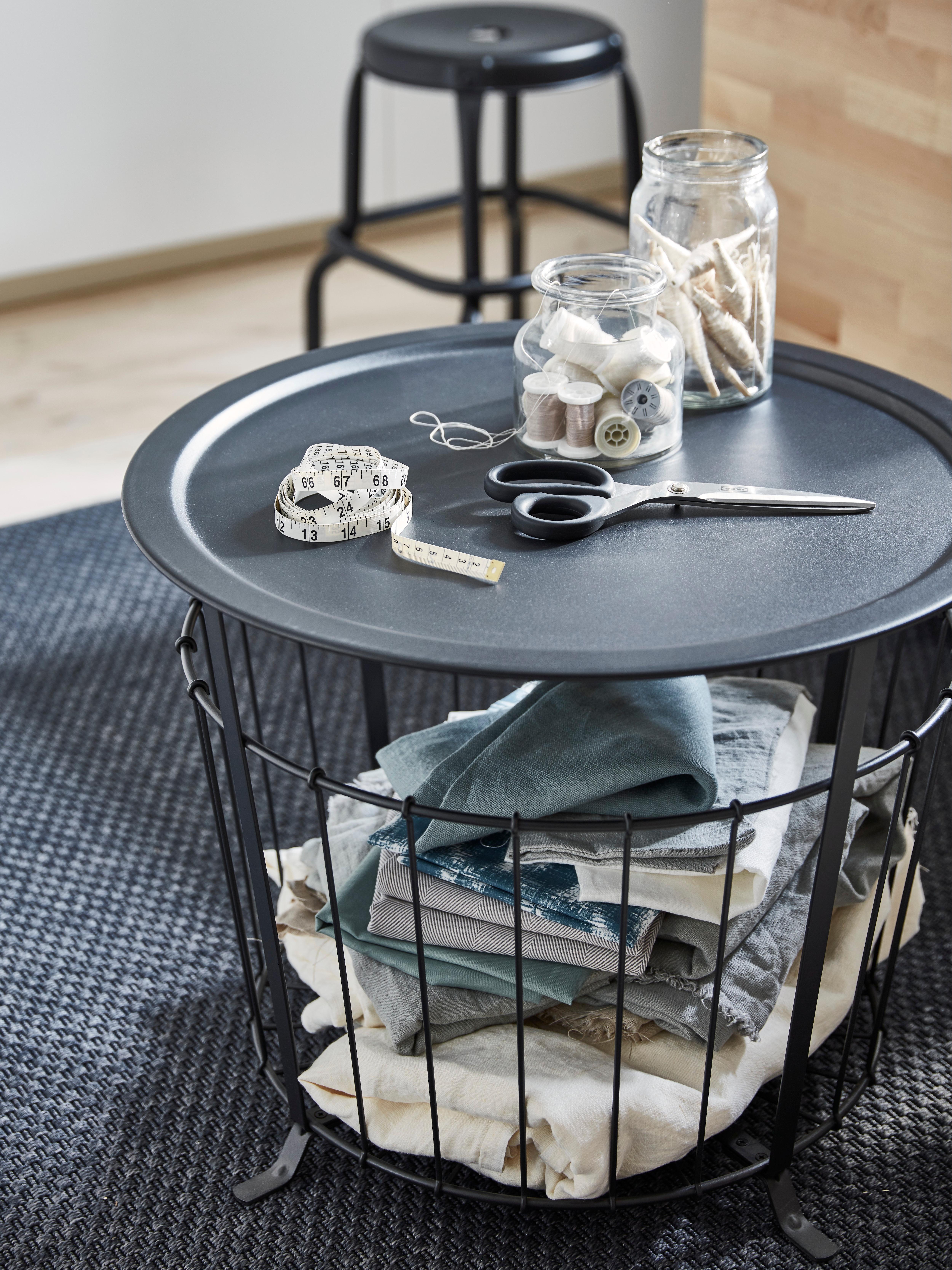 GUALÖV stol za odlaganje drži tkaninu. Na vrhu su staklenke pune konaca, škare i traka za mjerenje.