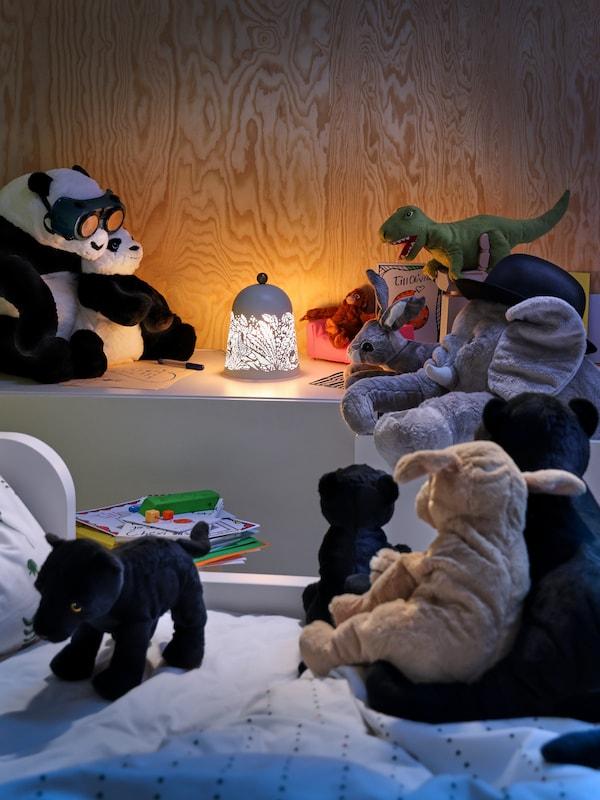 Des peluches JÄTTELIK, DJUNGELSKOG et GOSIG réunies autour d'une lampe de table à DEL SOLSKUR dans une chambre d'enfant.