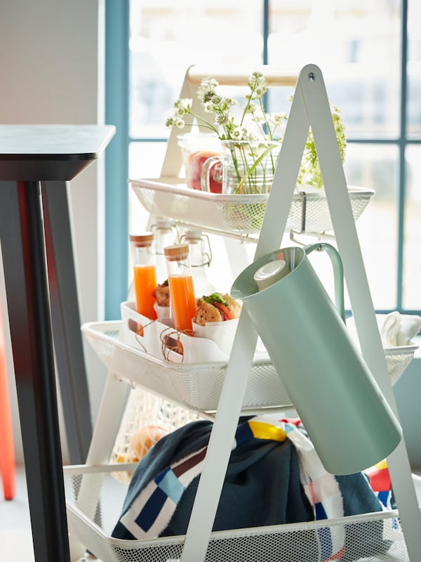 A white RISATORP steel cart with a wooden handle, filled with a complete breakfast for two.