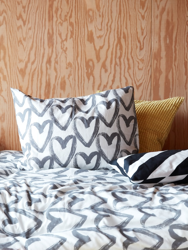 A bed with two cushions, and LYKTFIBBLA quilt cover and pillow case with gray hearts on a white background.