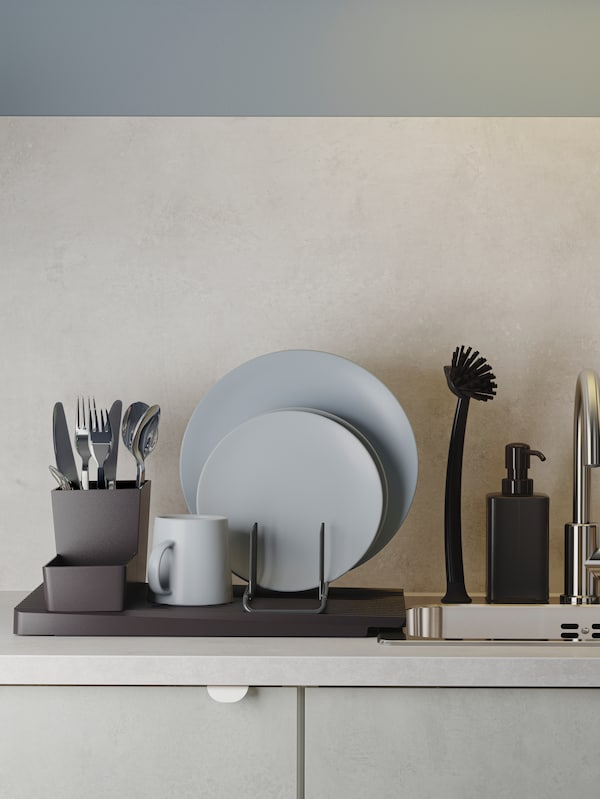 A black dish drainer with grey-blue dinnerware and cutlery stands next to an inset sink in stainless steel.