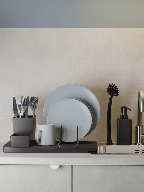 Černý odkapávač na nádobí  s šedomodrým nádobím a příbory stojí vedle zapuštěného dřezu z nerezavějící oceli.