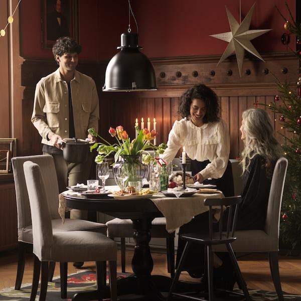 Muž a dvě ženy u kulatého jídelního stolu s čalouněnými židlemi a závěsným světlem.