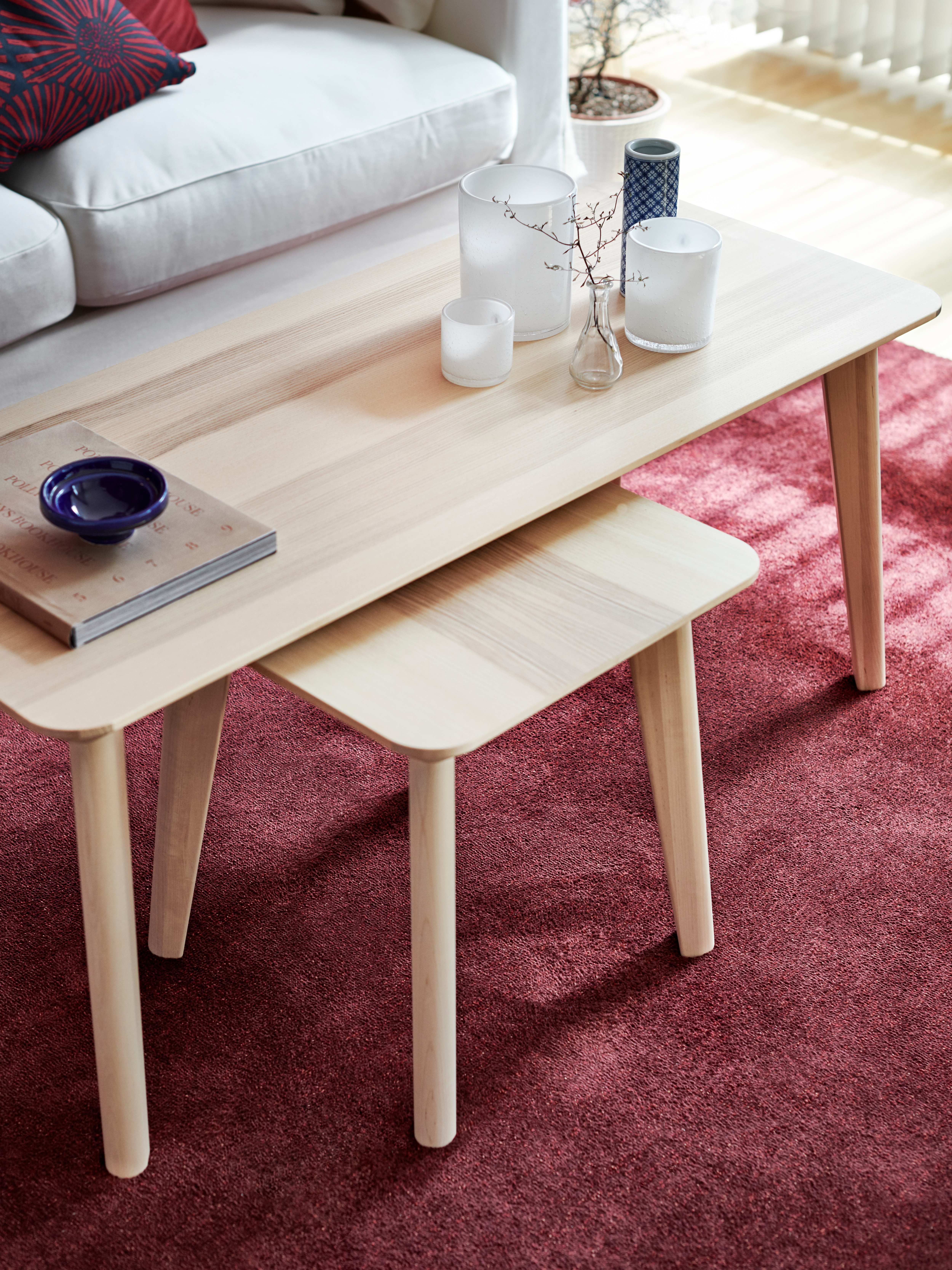 A LISABO table in ash veneer with a wooden stool beneath it, various items on the table and a pink rug under it.