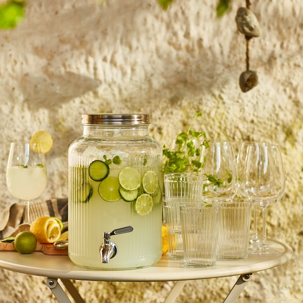 A garden table with a VARDAGEN tap jar filled with garnished lemonade, surrounded by STORSINT glasses and sliced citruses.