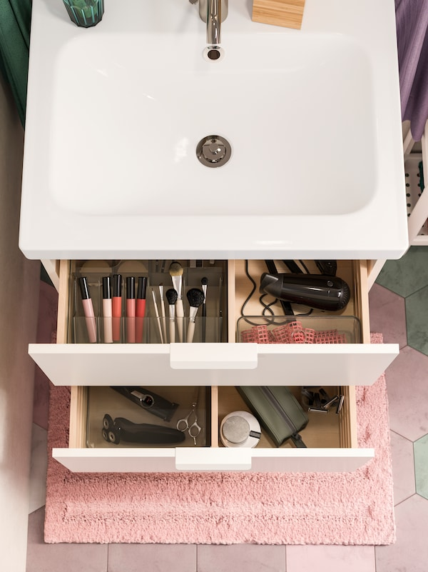 A white wash-stand with two open drawers. Inside are smoked see-through boxes that help organise makeup and more.