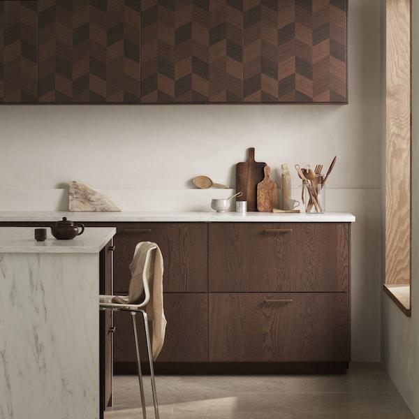 مطبخ به خزائن حائط بني مزركشة، وخزائن قاعدة بواجهات أدراج بني وأسطح عمل شكل رخامي.