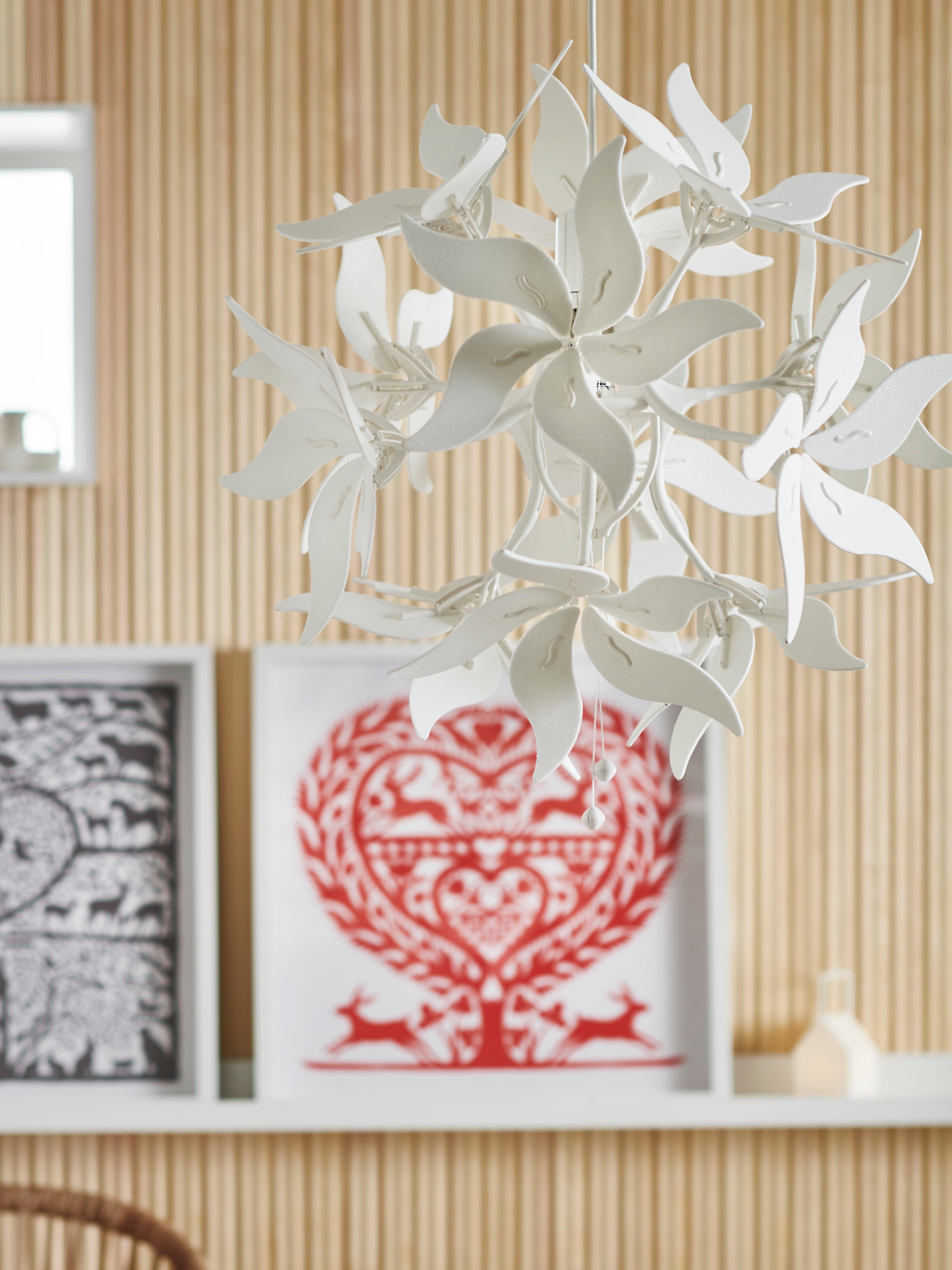 Forma geometrikoa duen sabaiko lanpara zuriaren xehetasuna, marko zuriak hormako apal zurian, dekorazio-objektua, egongelan.