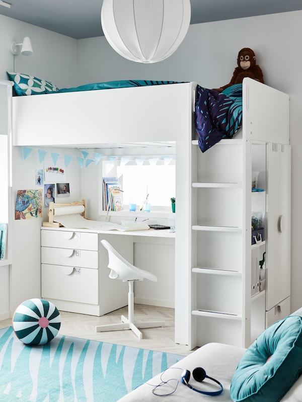 Hvid loftseng med sengetøj i turkis, et skrivebord og en kontorstol nedenunder med hobbyudstyr, en blå guirlande og et blåt tæppe.