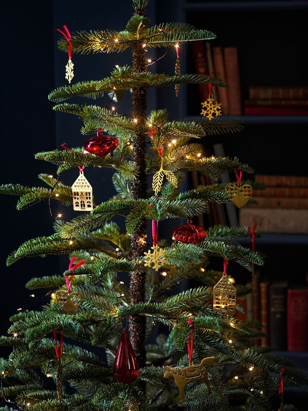 An artificial holiday tree lit up with lights and decorated with gold decorations shaped like houses and red baubles.