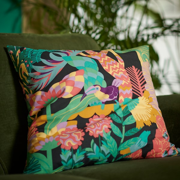 A colourful NÄBBFLY cushion cover featuring a tropical bird among lush greenery and plants on a green velvet sofa.
