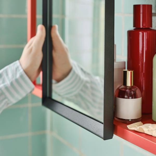 Una mano apre un'anta a specchio al centro di una struttura da parete ENHET con flaconi di profumo sui ripiani a giorno.