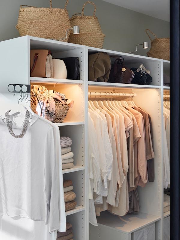 Uma combinação de arrumação PLATSA em branco, composta por unidades de diferentes alturas, debaixo das escadas numa casa.