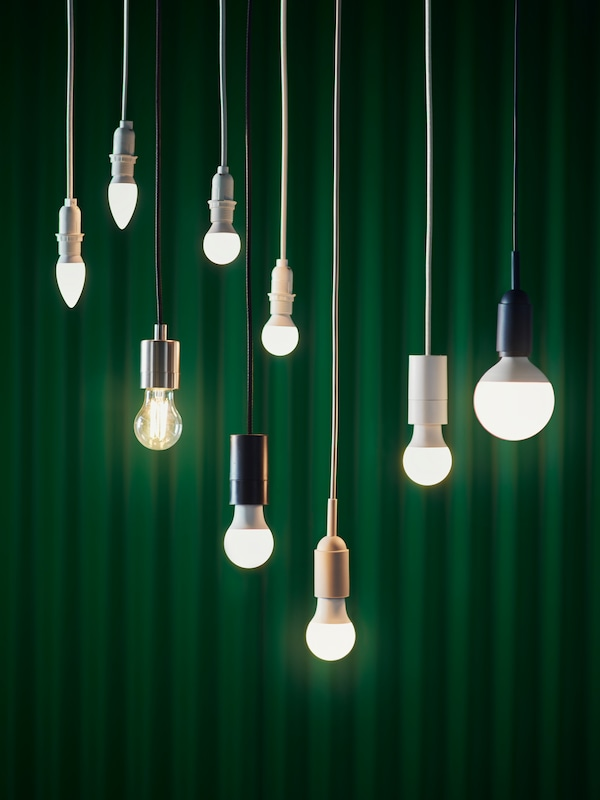 Nine SOLHETTA LED bulbs, which are in different sizes and shapes, are hanging in front of a dark green background.