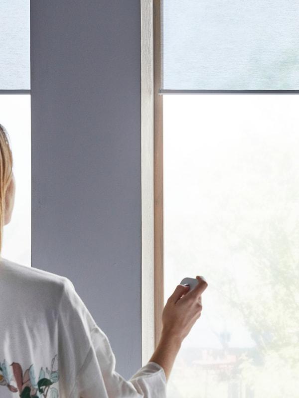 Žena s diaľkovým ovládačom sťahuje rolety KADRILJ počas slnečného dňa.