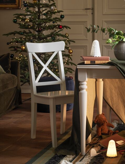 A white INGOLF chair at an INGATORP table in a holiday-decorated room. A cloth is over the table and soft toys are under it.
