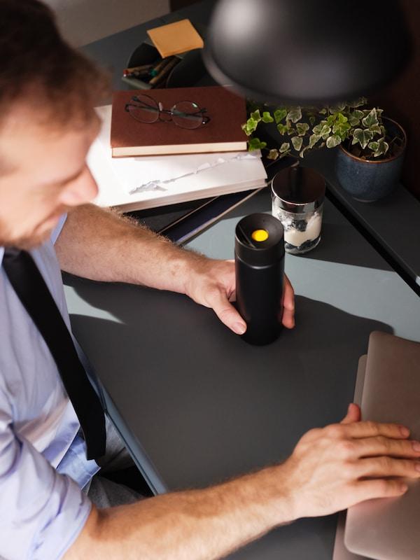 une homme assis à son bureau avec un thermos de café à la main
