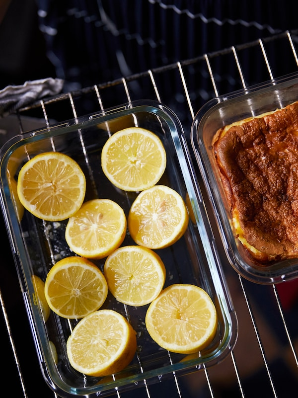 Halved lemons in a glass container beside another glass container with food inside, on top of a cooling rack.