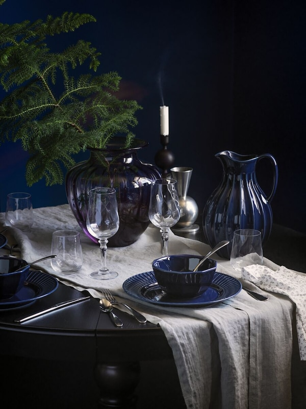 STRIMMIG bowls and plates in blue earthenware and KONUNGSLIG wine glasses, beside a blue carafe and a blue/clear vase.