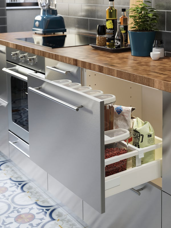 A stainless steel kitchen with a wooden worktop in oak/veneer. One drawer is open, dry goods are stored inside.