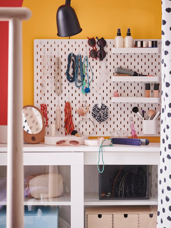A SKÅDIS pegboard on the wall with hooks and small shelves holding necklaces, bracelets, sunglasses and cosmetics.