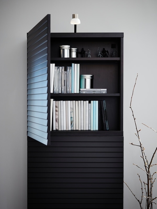 A cabinet with accent slatted doors in anthracite and a nickel-plated LED lamp on top, door is open, books are inside.