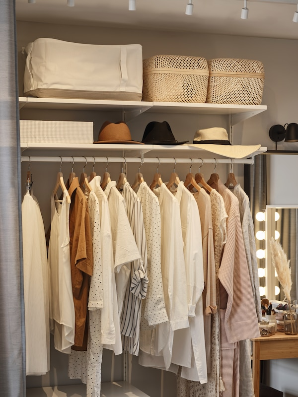 An open BOAXEL wardrobe with clothes hanging on a clothes rail. Hats and baskets sit on shelves above the hanging clothes.