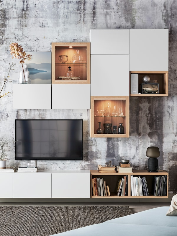 A TV on a wall above a white BESTÅ TV bench. BESTÅ cabinets with glass and white LAPPVIKEN doors are on the wall above.