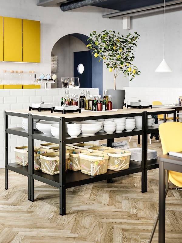 Banchi da lavoro neri con piani tavolo in legno, ciotole bianche, cestini verde oliva chiaro con matite e pennarelli, e condimenti.