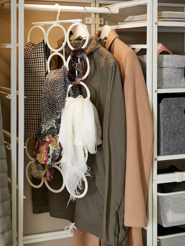 Coats and a white KOMPLEMENT multi-use hanger holding sunglasses and shawls hang beside shelves inside JONAXEL storage.