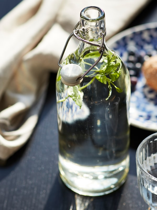 Gelas kaca jernih berisi air yang membuih terletak di atas meja. Sehiris buah lemon baru sahaja dibubuh ke dalam gelas.