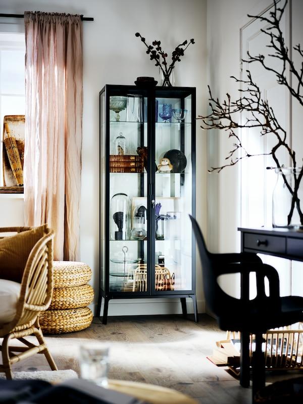 Une vitrine MILSBO remplie de différents objets, dans le coin d'un salon lumineux.