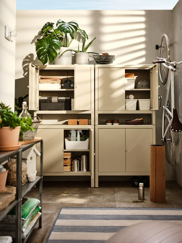 Four stacked beige KOLBJÖRN cabinets with four doors open showing items inside, plus various plants and a hanging bicycle.