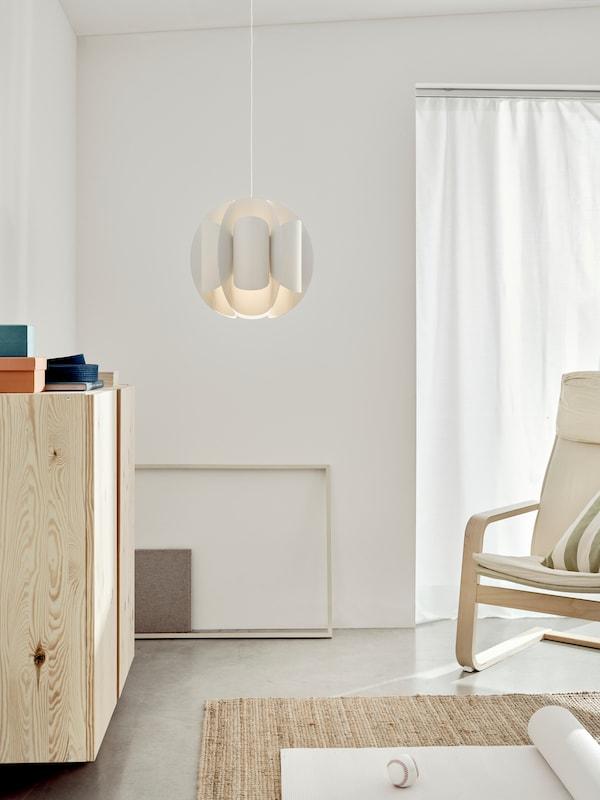 Egy világos, modern nappaliban járunk, amely a középpontjában egy mennyezetről lógó TRUBBNATE függőlámpaernyőt látunk.